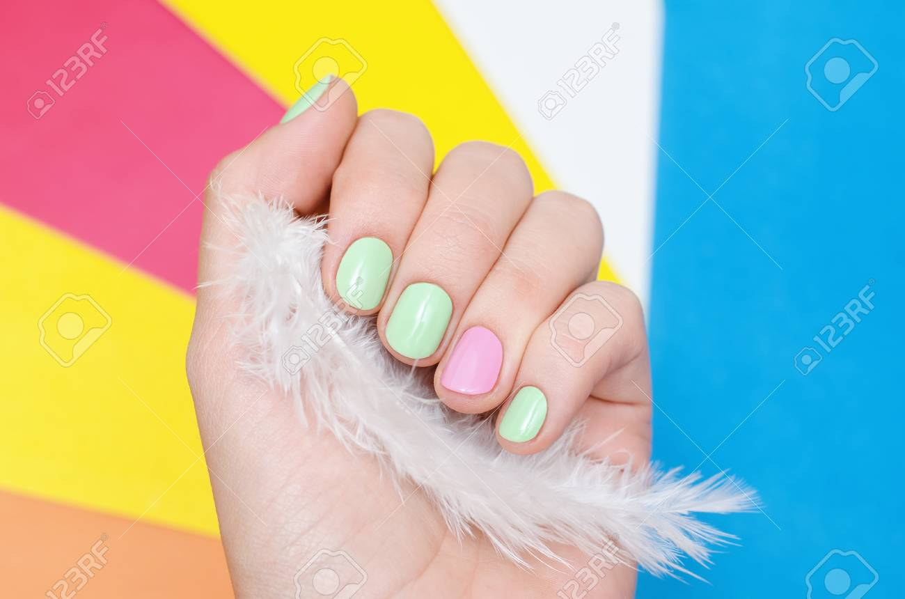 Beautiful Female Hand With Light Green And Pink Nail Design On