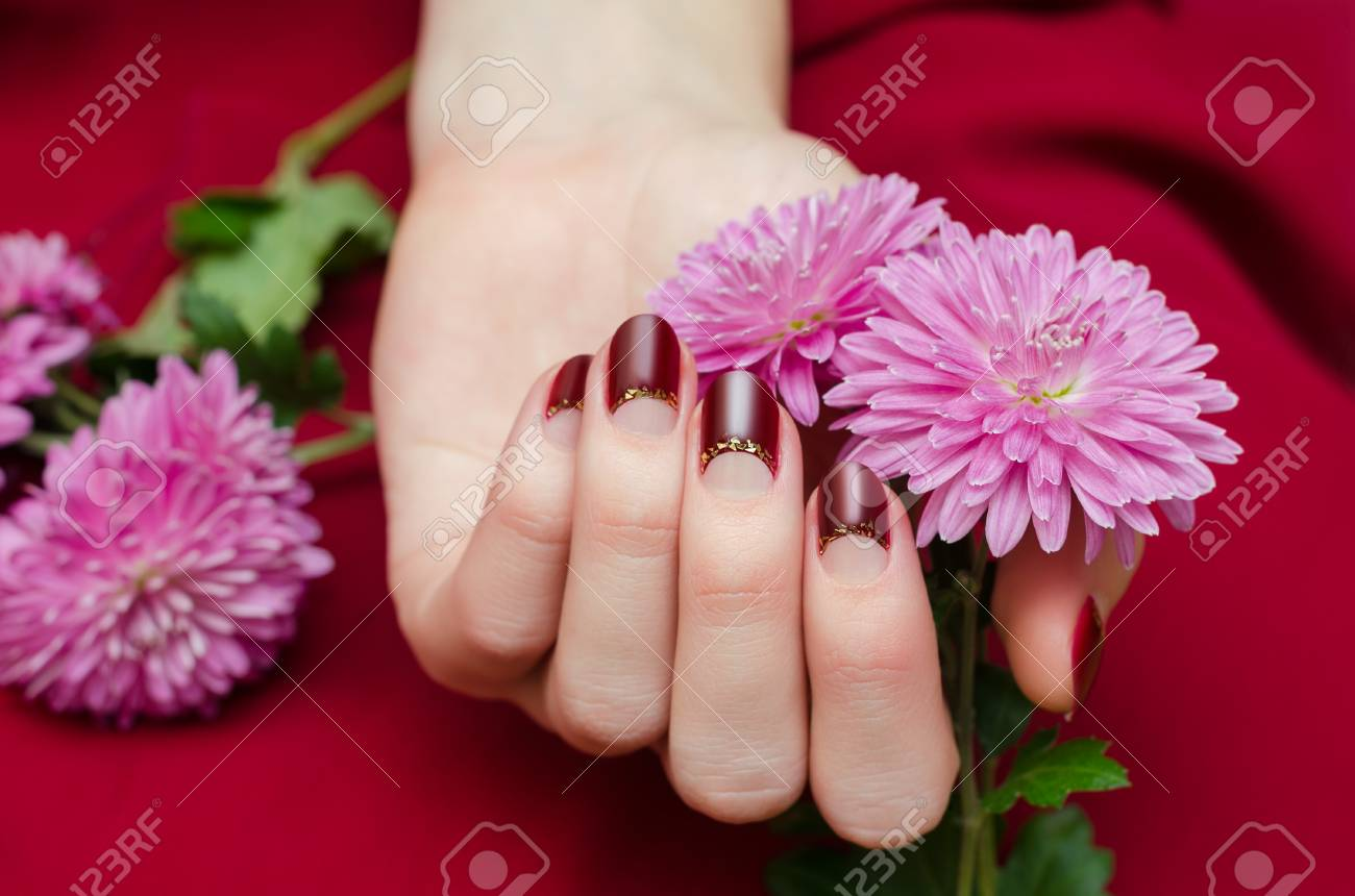 Female Hands With Dark Red Nail Design Holding Flowers. Stock Photo ...