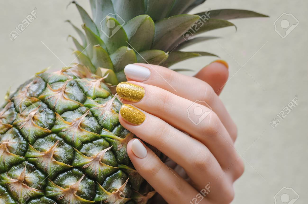 Female Hands With White And Gold Nail Design Holding Pineapple Stock