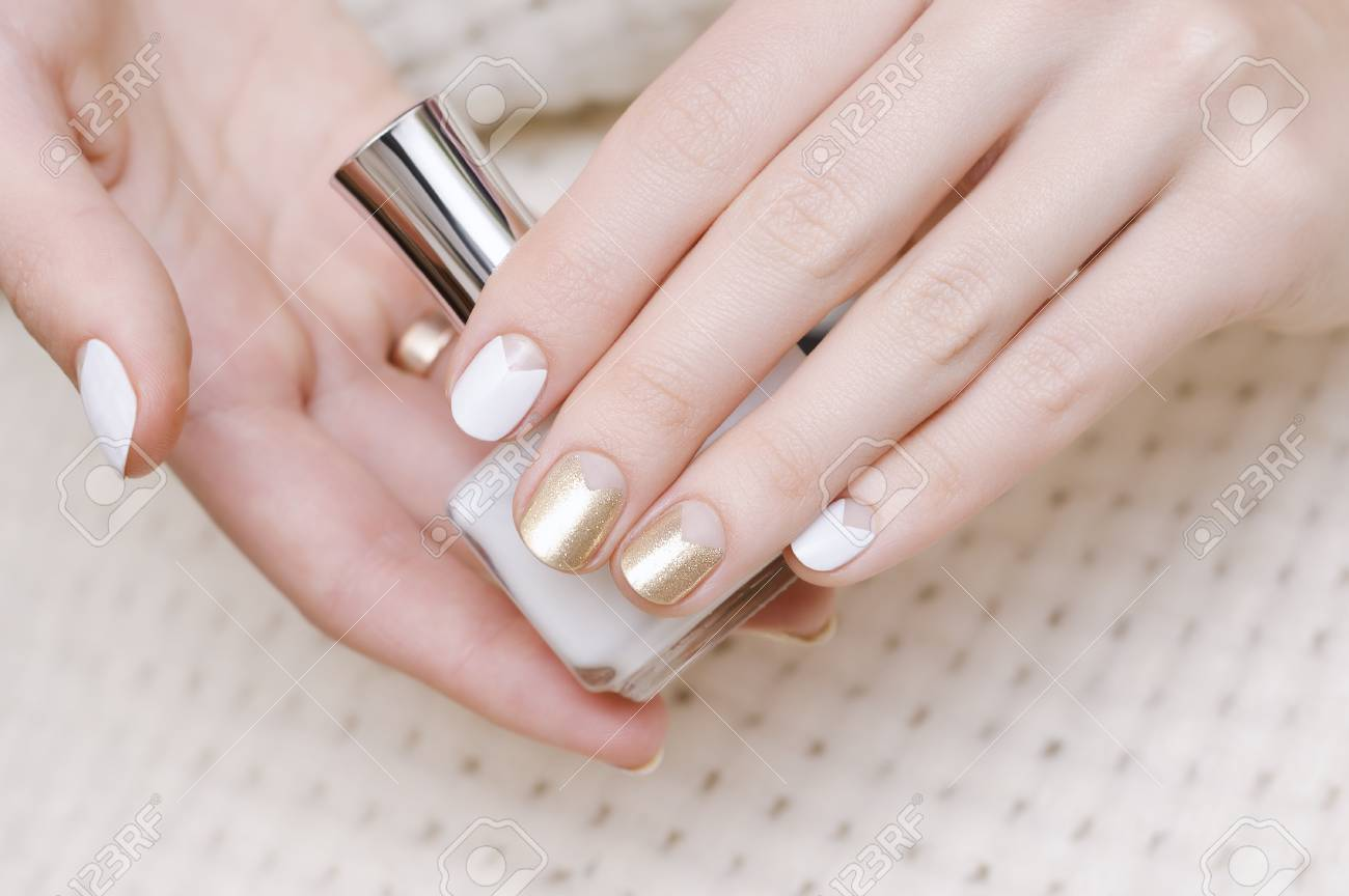 Female Hands With White And Gold Nail Design Holding Nail Polish