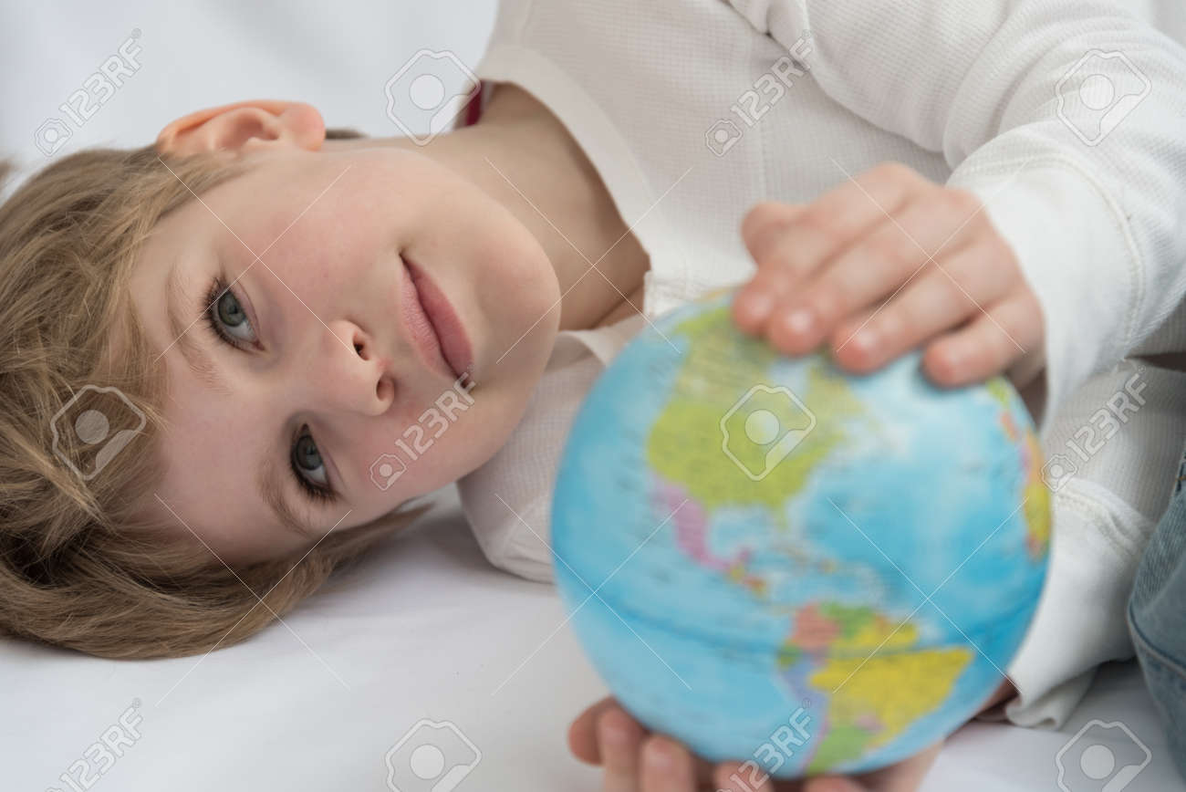The child dreamily examines the globe. Travel yearning concept. Closed borders and quarantine. A European-looking child dreams of travel - 168593026