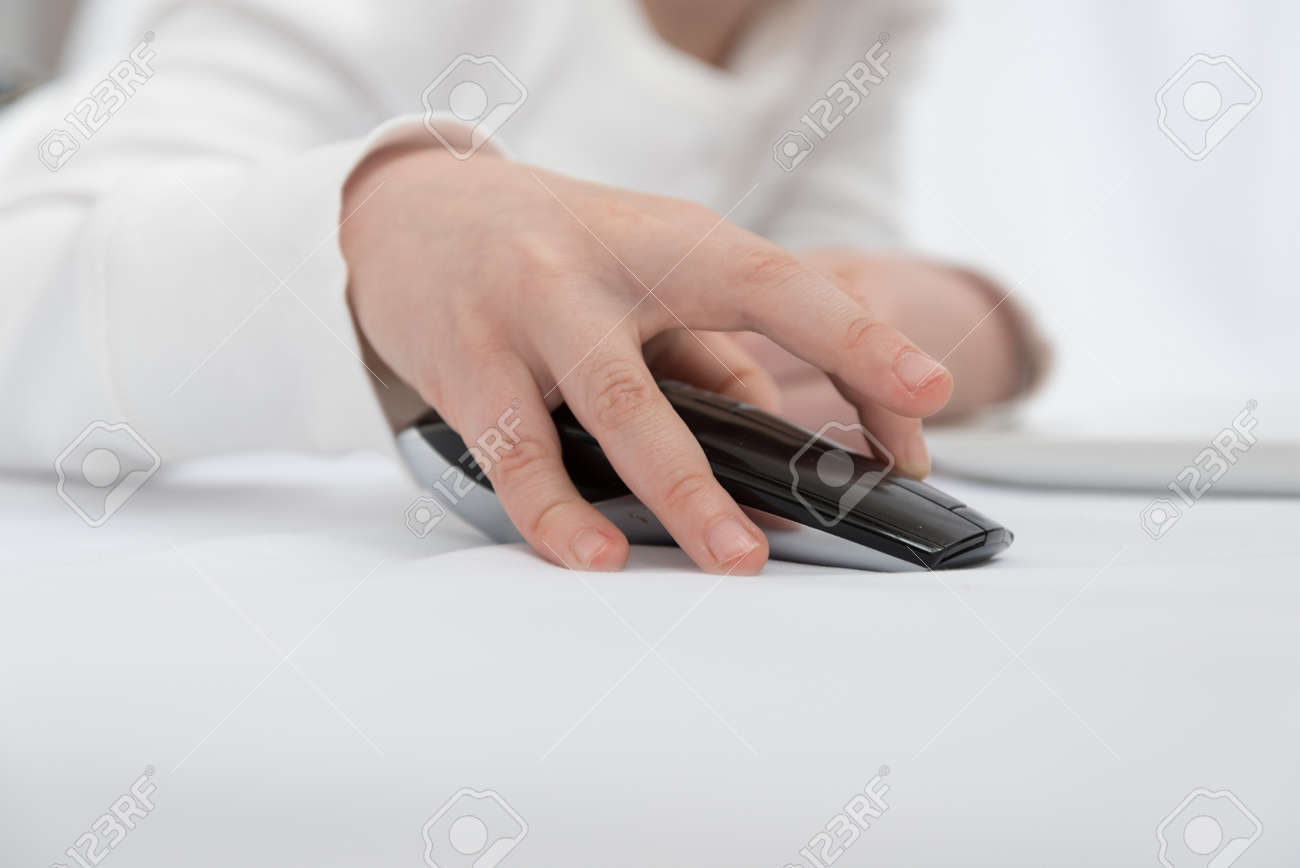 Childrens hand close up. The child is engaged or plays in the laptop using a wireless mouse - 168593046