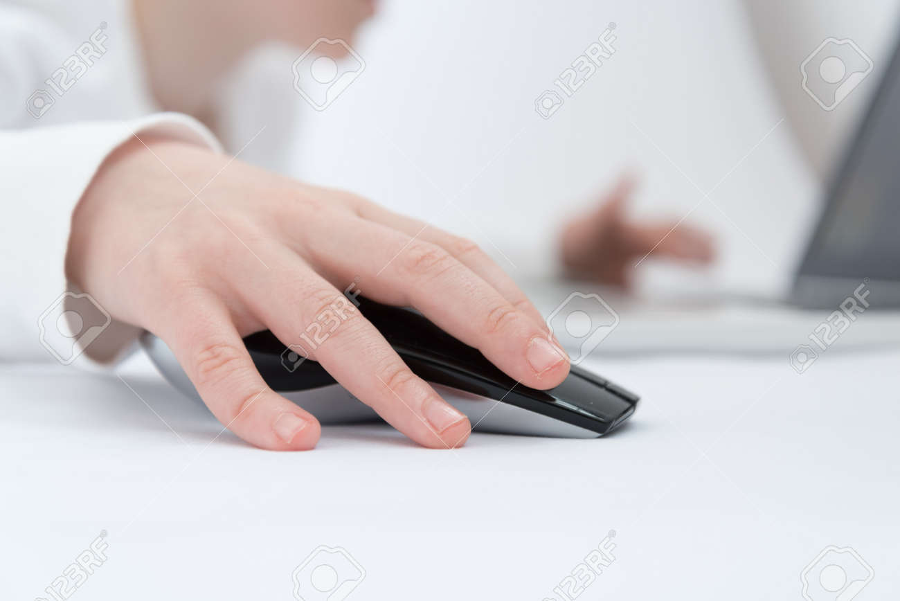 Childrens hand close up. The child is engaged or plays in the laptop using a wireless mouse - 168593053