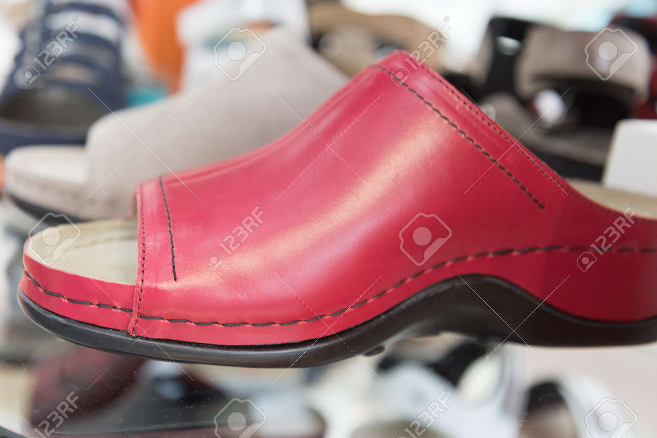 The shop window displays comfortable orthopedic shoes. Modern style red leather shoes. Taking care of your feet. Prevention and treatment of flat feet - 167412652