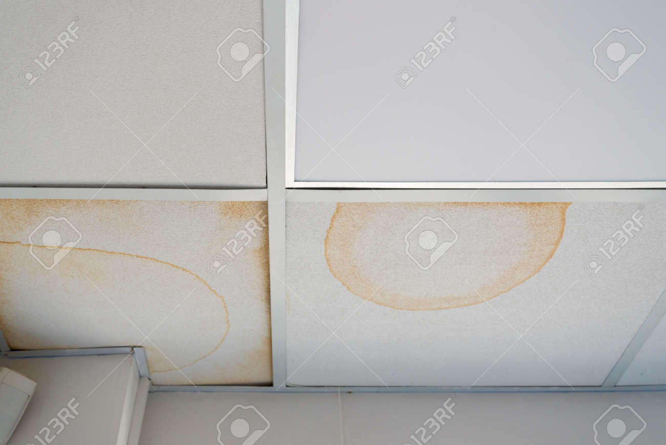 False ceiling leaks. Yellow dirty stains from the pipe break. Emergency situation, destruction of the roof - 168593084