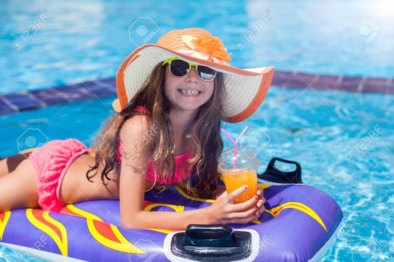 Kid girl in the pool has fun. Children and summer concept - 131196056