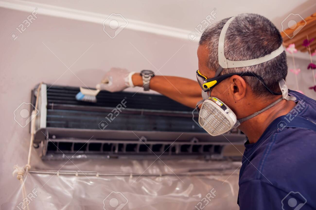 Man worker doing professional cleaning of air conditioning. - 149929461