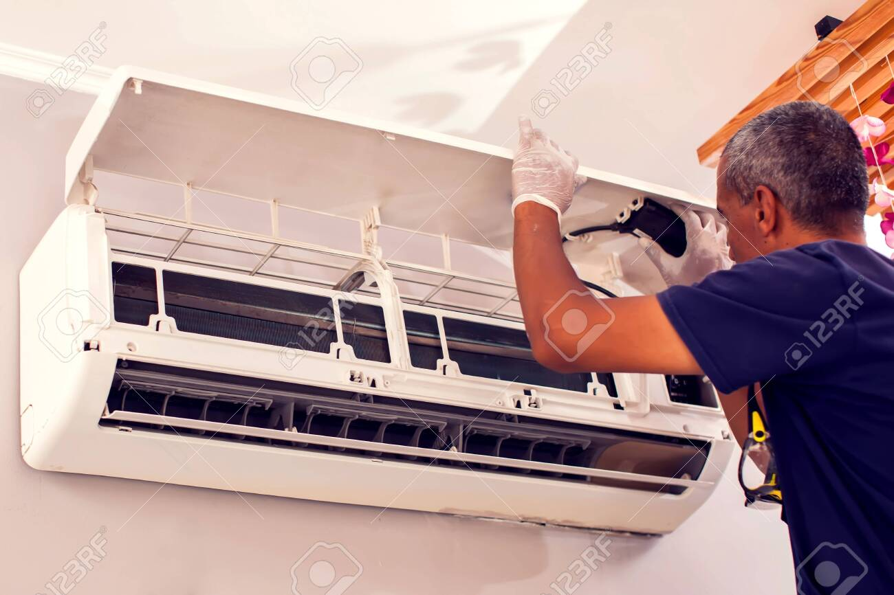 Man worker fixing air conditioning on the wall. Professional service - 149929314