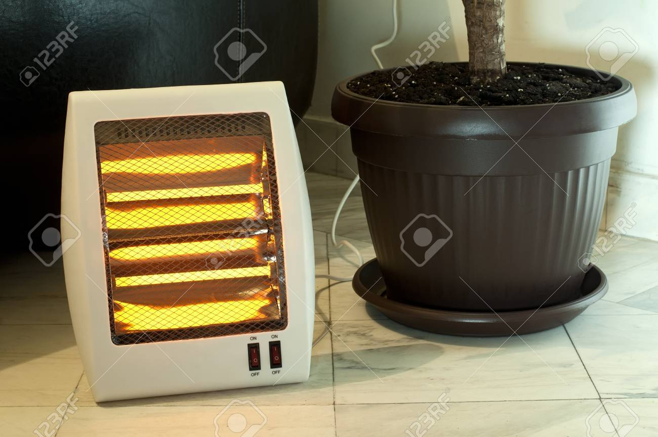 123RF.com & Electric heater with halogen coils. Flower pot and heater on..