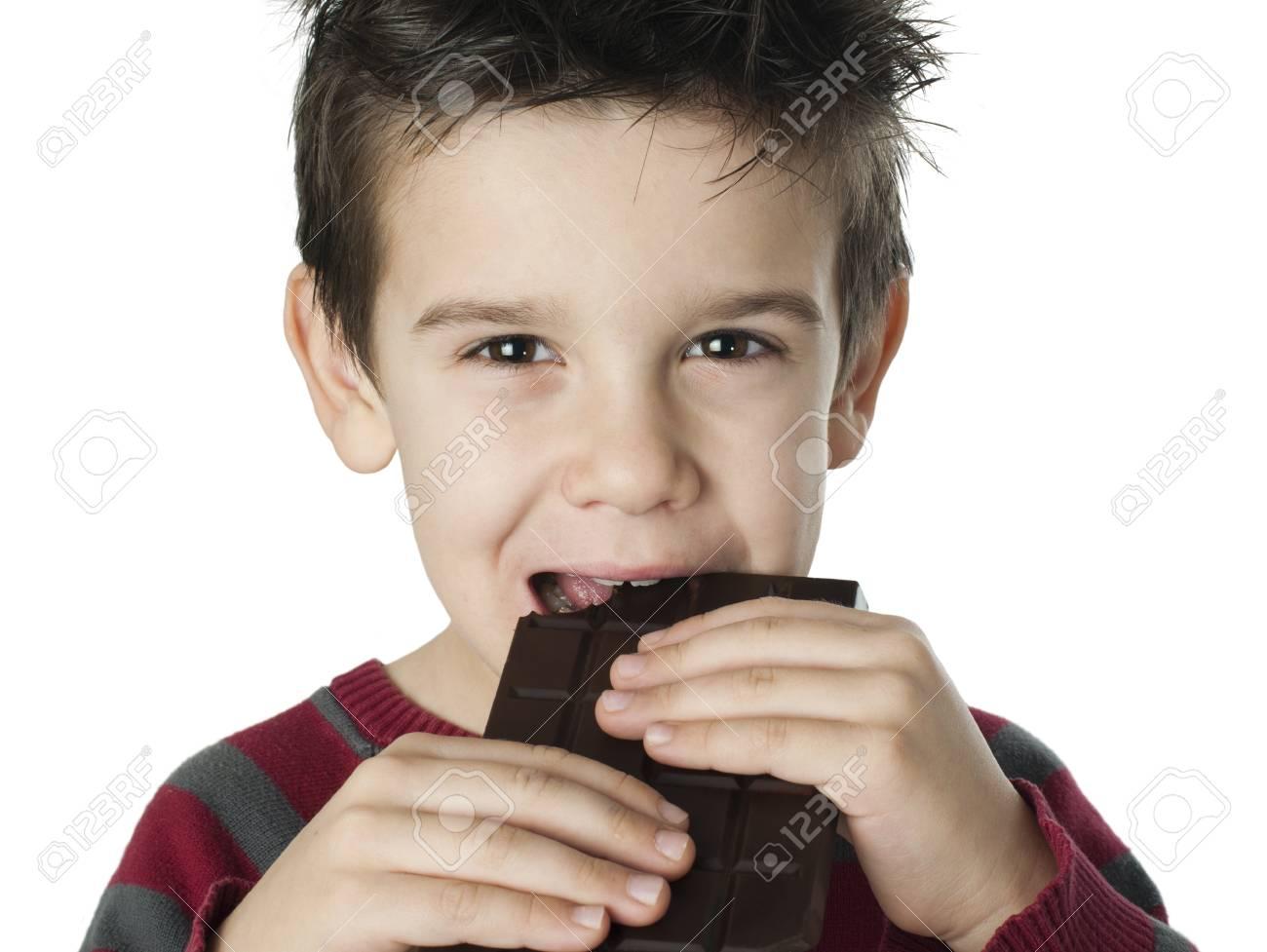 Smiling little boy eating chocolate. White isolated Stock Photo - 16791191