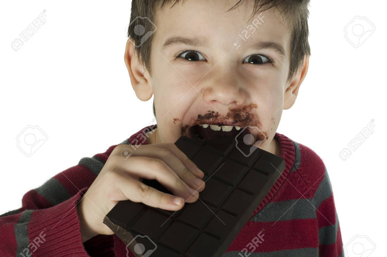 Smiling kid eating chocolate. Smeared stained with chocolate lips. White isolated Stock Photo - 16791365