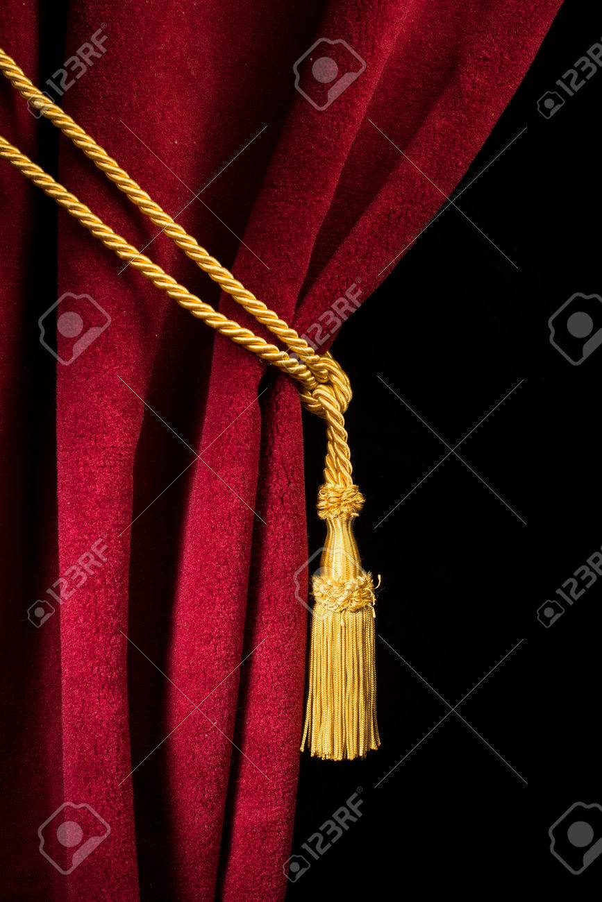 Red velvet curtain with tassel. Close up black isolated curtain - 25310039
