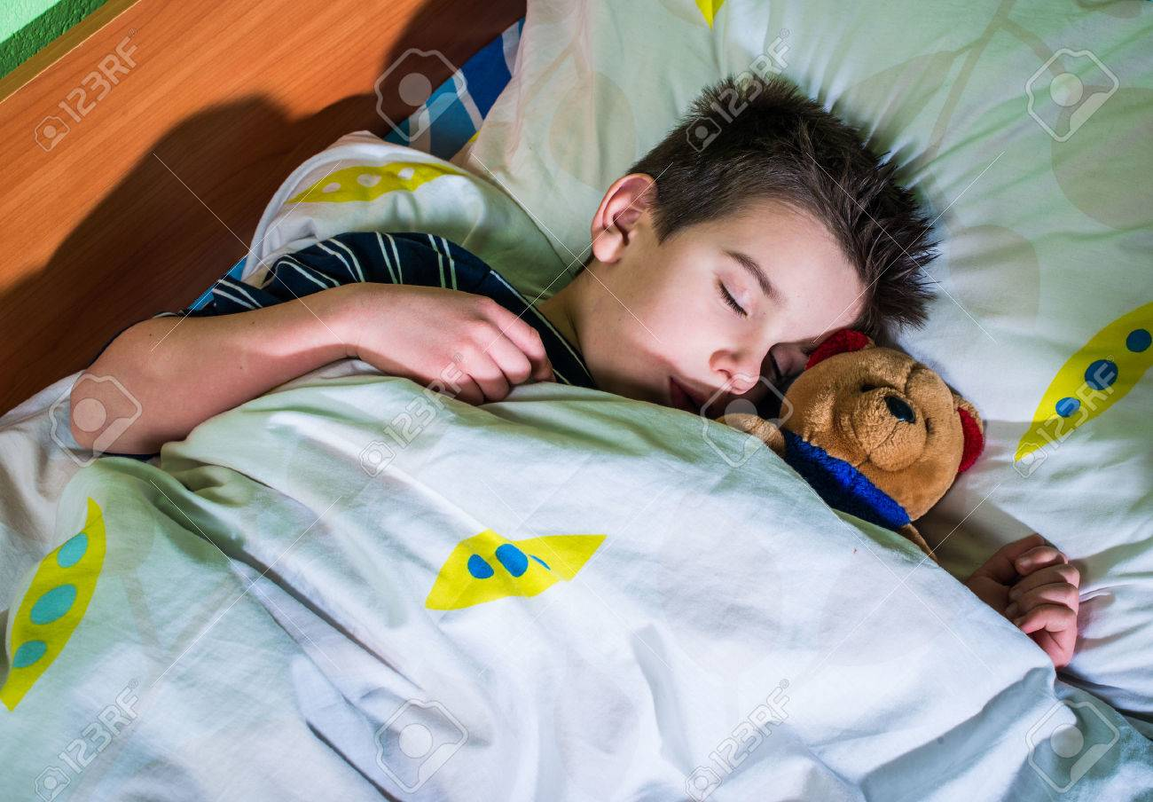 Sleeping child with his toy bear. - 25631272