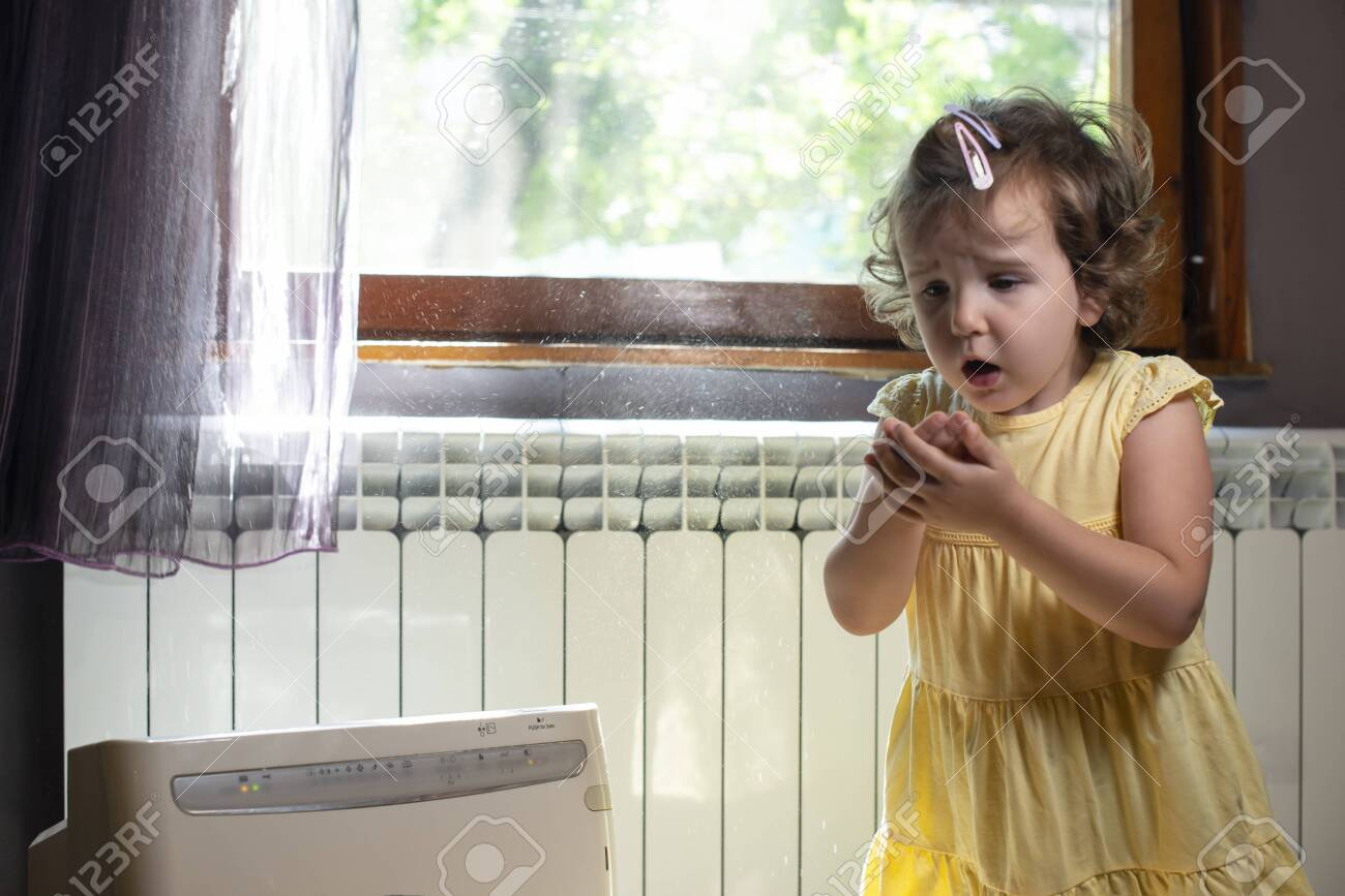 Little girl in a dusty room. Air purifier and coughing kid. Dust in the air. Allergy concept. - 128382800