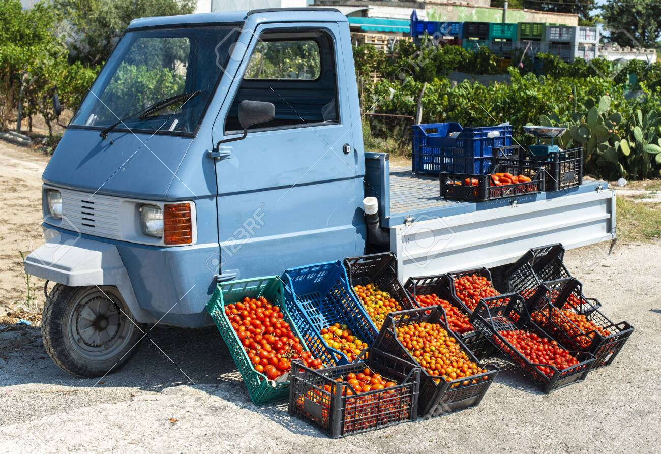Small italian apo truck with tomatoes. Street market. Farmer sale tomatoes on the street in Italy. - 131706798