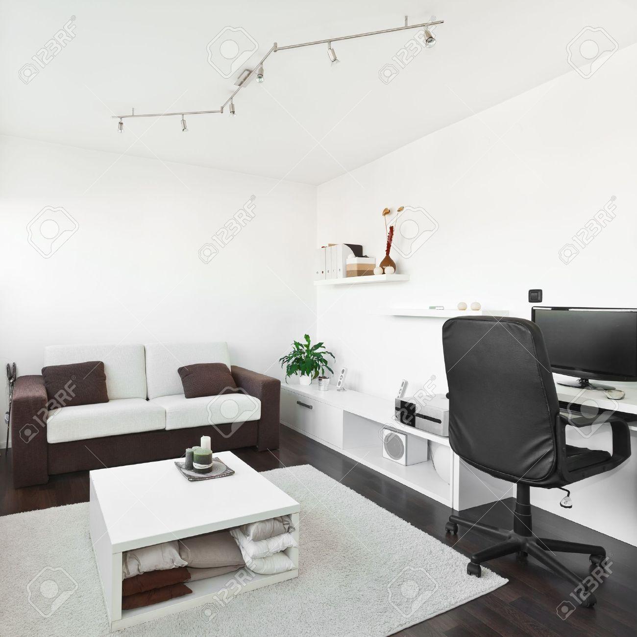 Moderne woonkamer met computer bureau en het scherm, bank en tafel ...