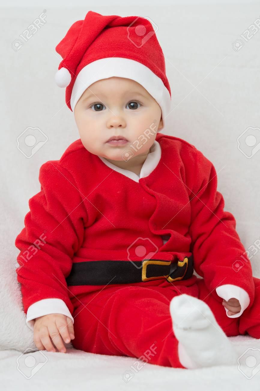Archivio Fotografico - Sette mesi di età bambina in Babbo Natale vestito  che si siede su una coperta bianca 1b3cf5f8d88