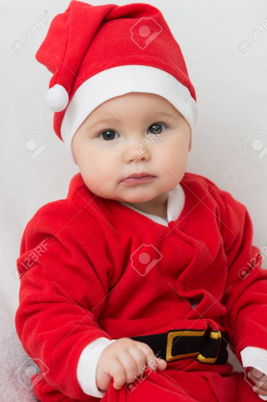 48e28af9e Seven months old baby girl in Santa Claus dress sitting on a white blanket,  looking