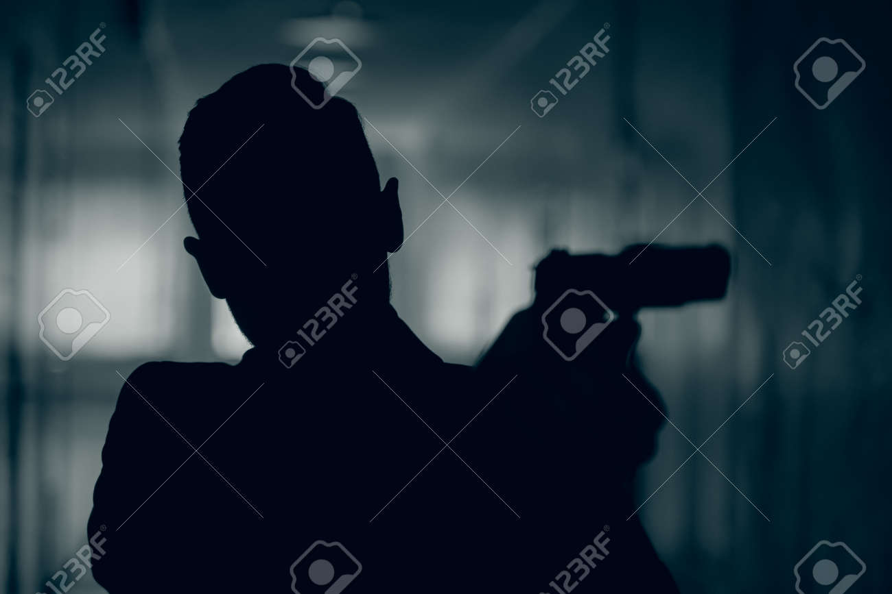 Silhouette of a man with a gun in a dark corridor, close-up. - 165657666
