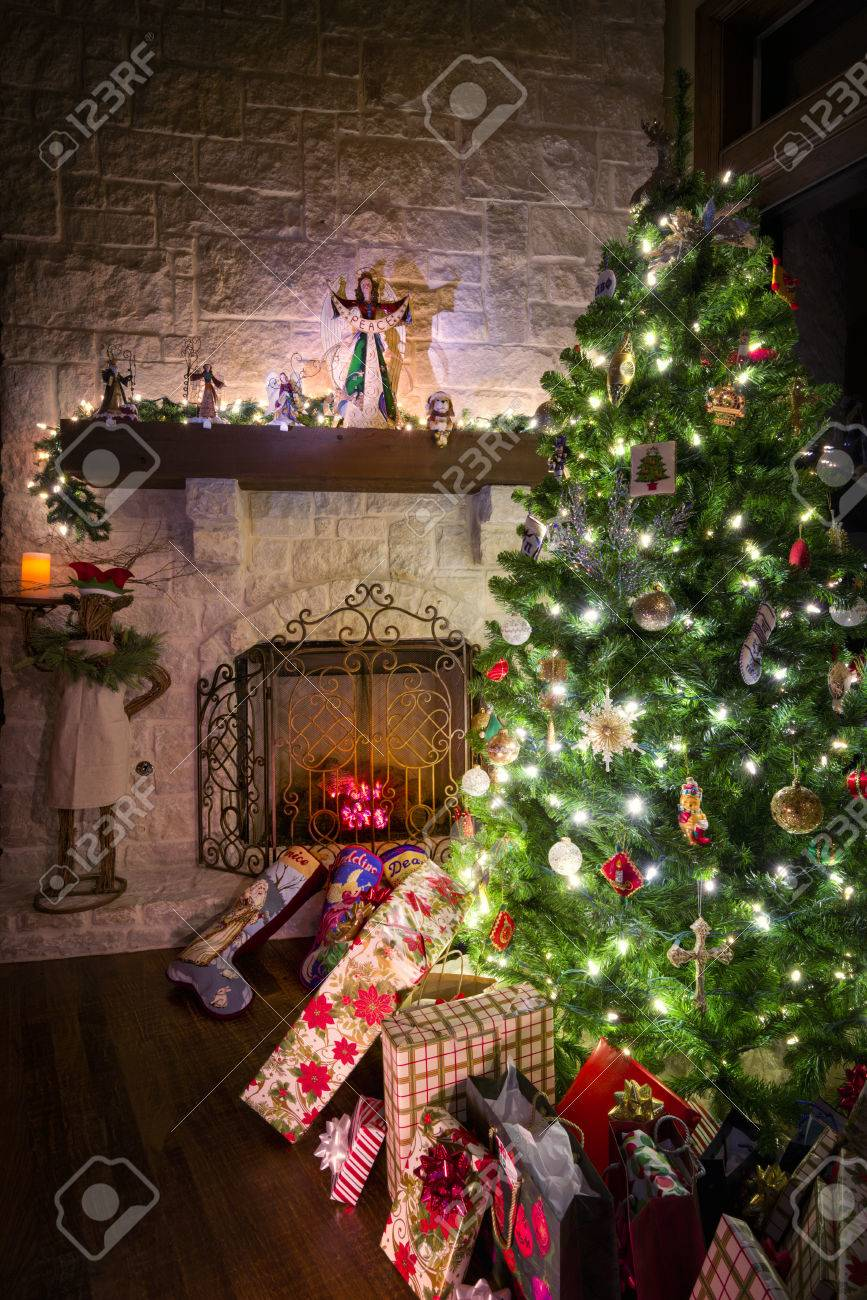 cozy christmas scene featuring a fireplace gifts and a decorated