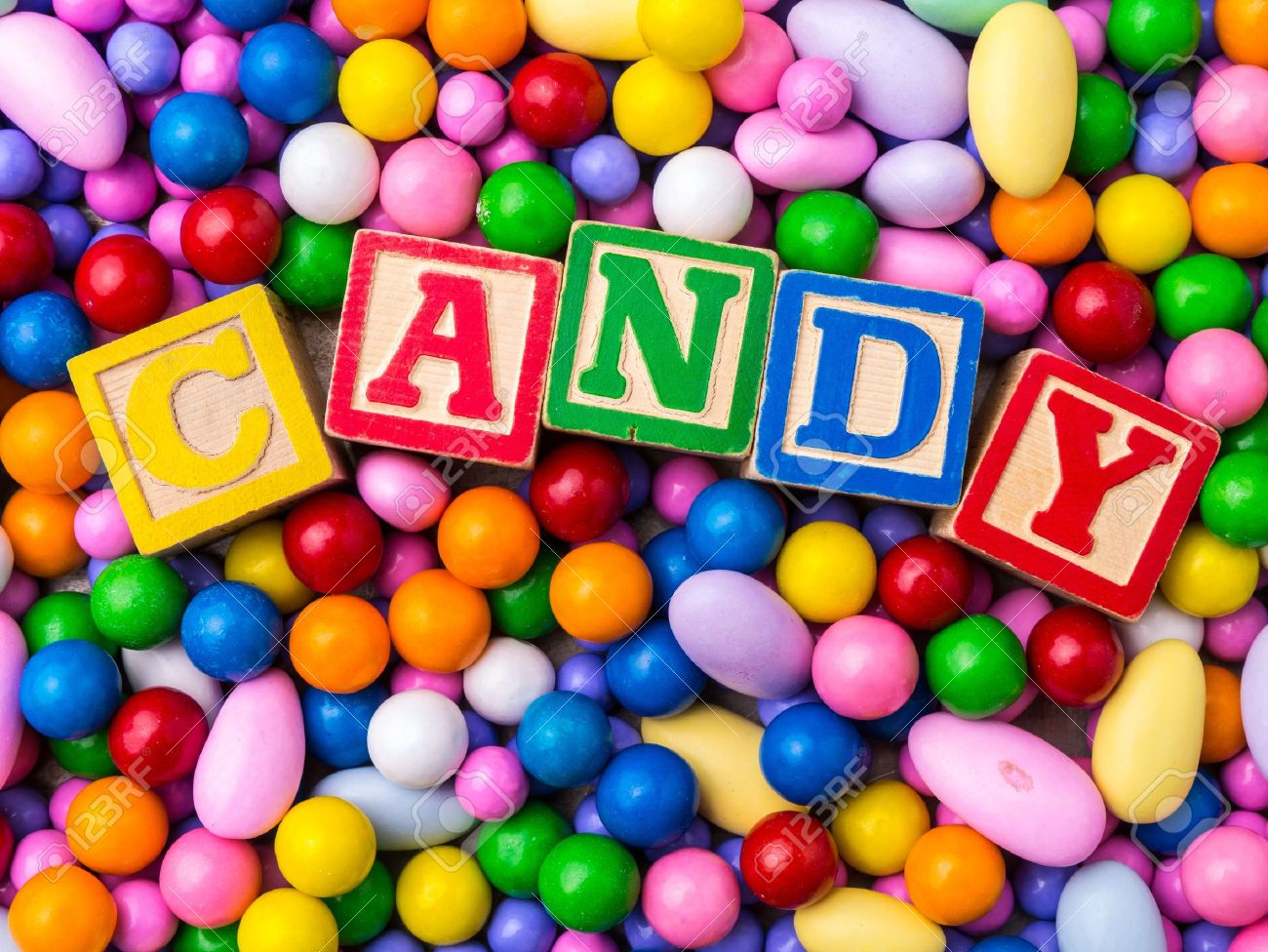 candy spelled out in alphabet blocks with colorful candy background