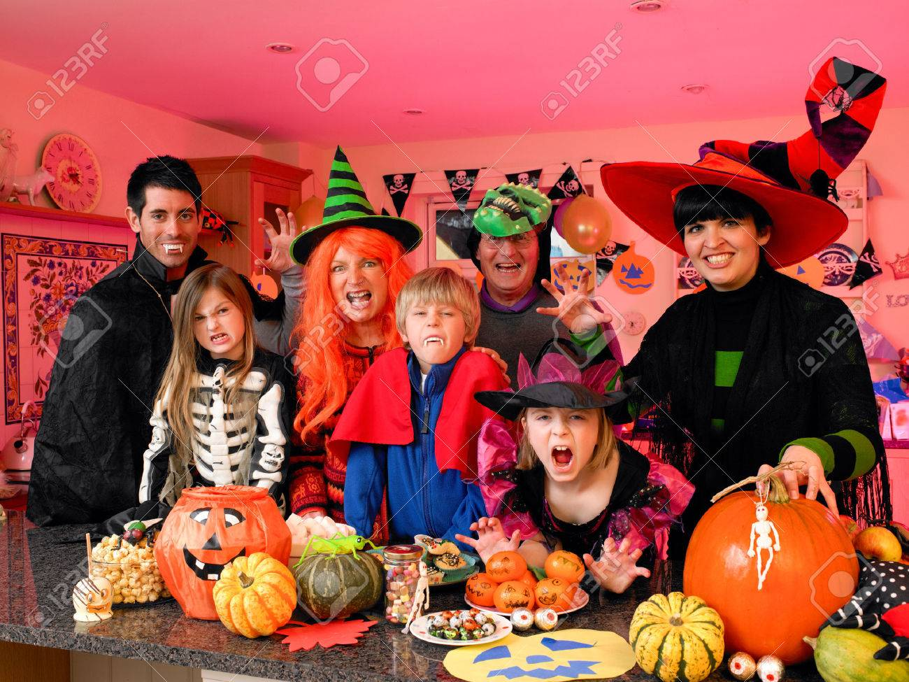 Familyfriends posing for the camera in their halloween costumes. They are standing in the kitchen with party food and treats set out in front of them. - 42278245