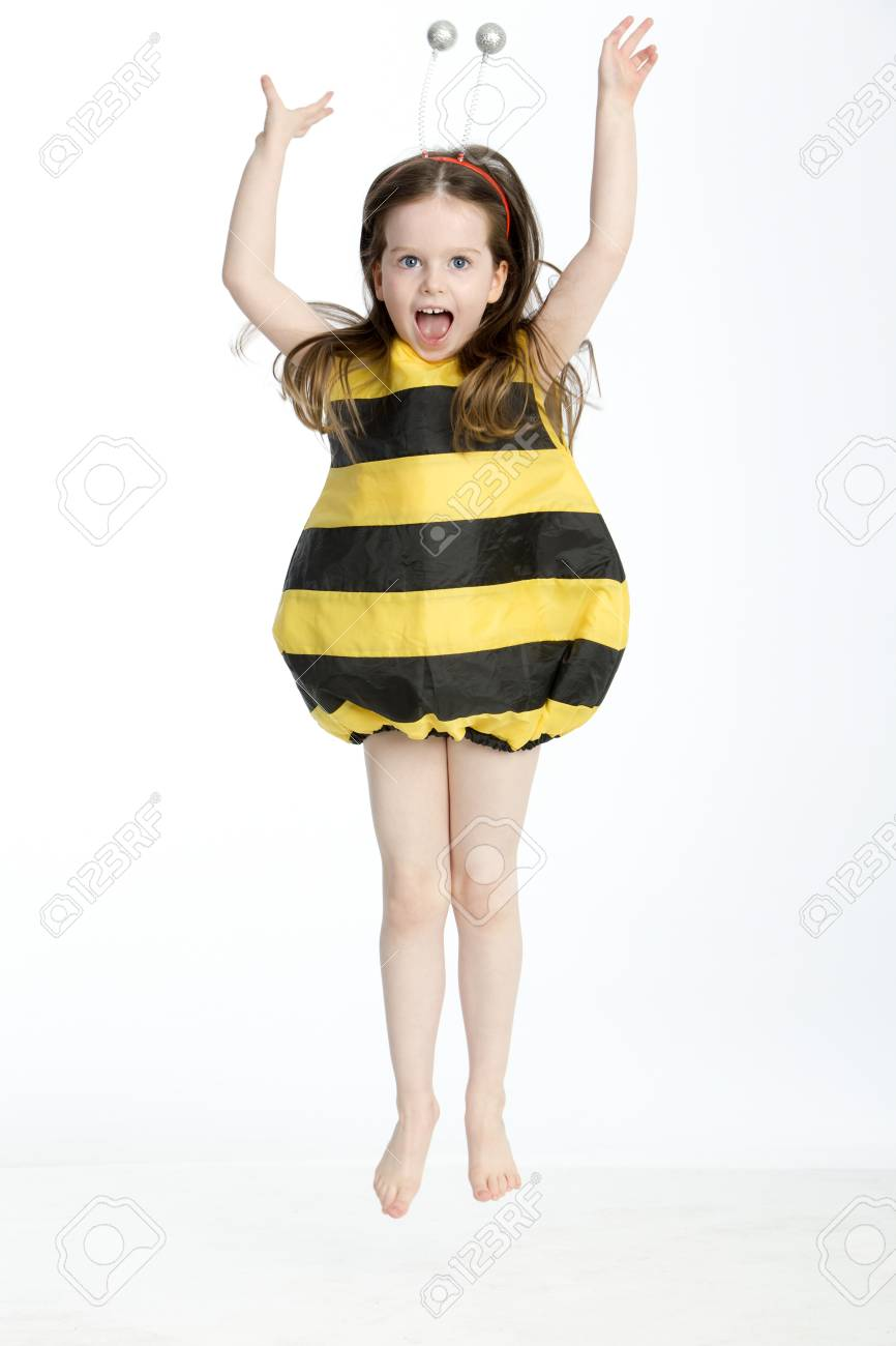 Little Girl In A Bumble Bee Costume Posing In Midair Against Stock