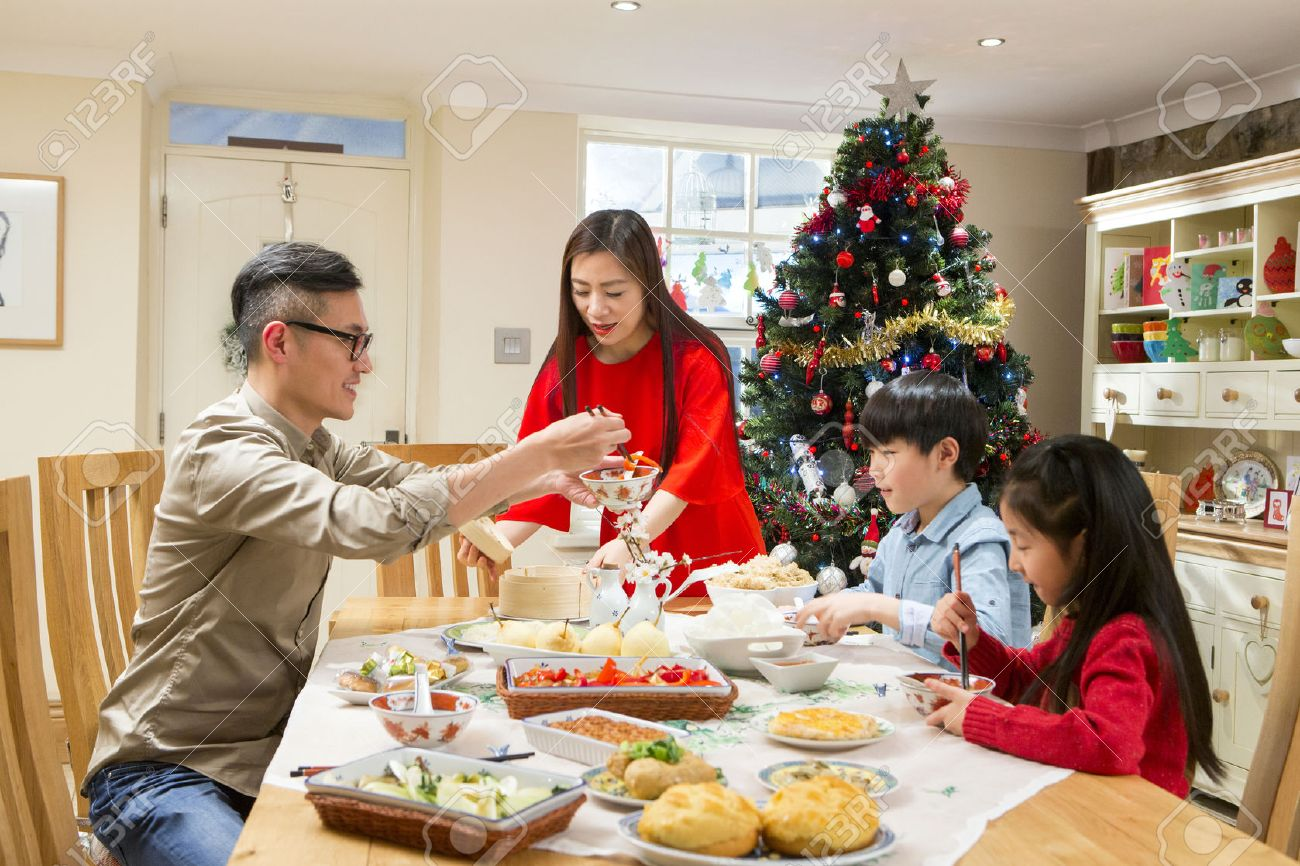 Chinese family enjoying their ~christmas dinner. They are eating traditional Chinese food. The parents are serving it round the table. - 58332008