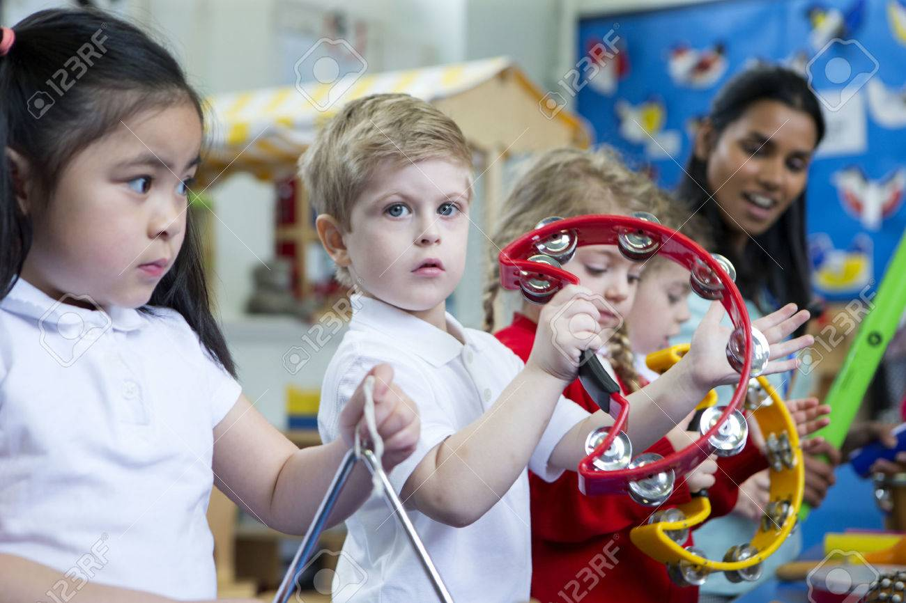 Nursery children playing with musical instruments in the classroom. One little boy is looking at the camera with a tambourine. - 60255492