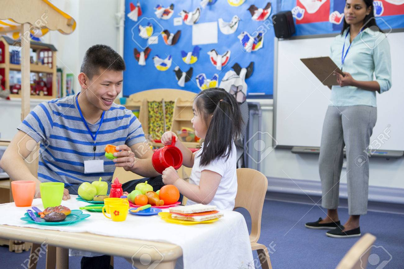 Male teacher playing in a toy kitchen with a nursery student. There is a teacher in the background with a clipboard who is watching them. - 60255927