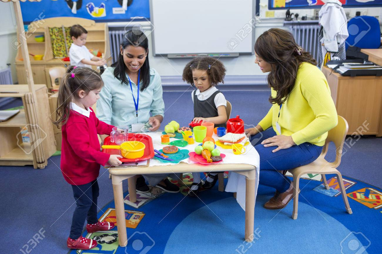 Teachers playing with plastic kitchen toys with their nursery students in the classroom. - 60255928