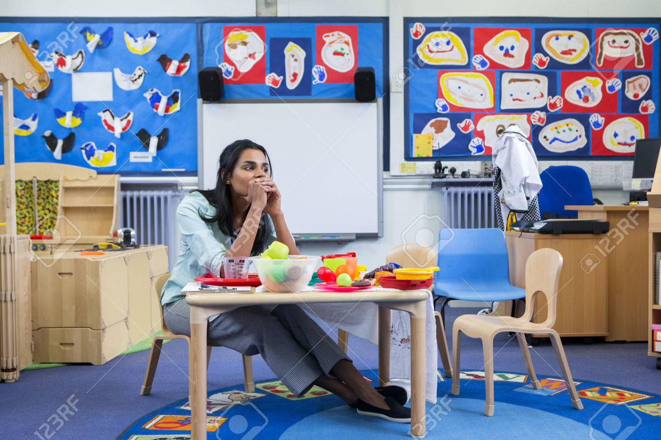 Stressed nursery teacher in a classroom. She is sitting at the toy table. - 60255931