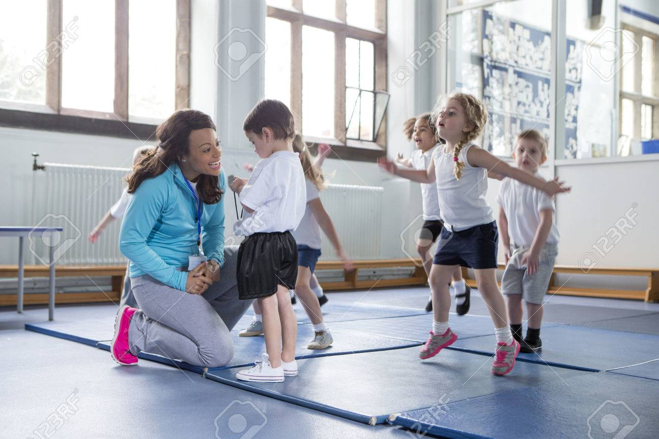 Nursery teacher reassuring one of her students during a physical education class. - 60255934