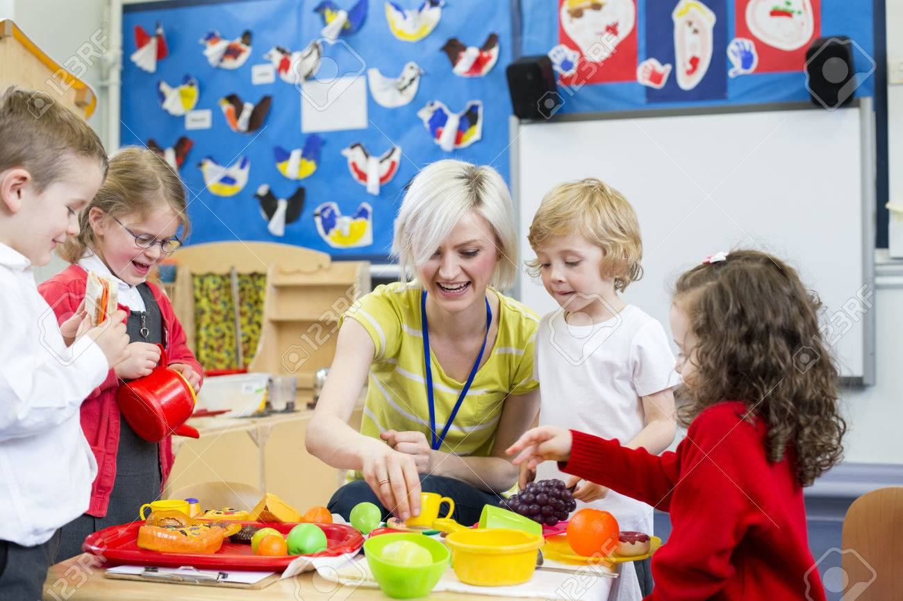 Nursery teacher playing kitchen roleplay with her students in the classroom. - 60255960