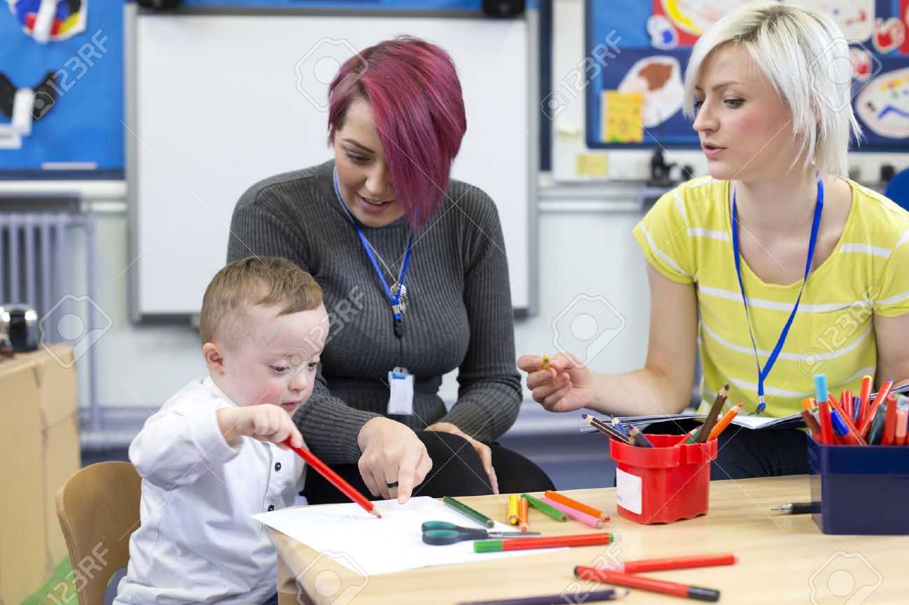 Nursery teacher sitting with a parent and her Down Syndrome son in the classroom. they are discussing the little boys progress. - 60255962