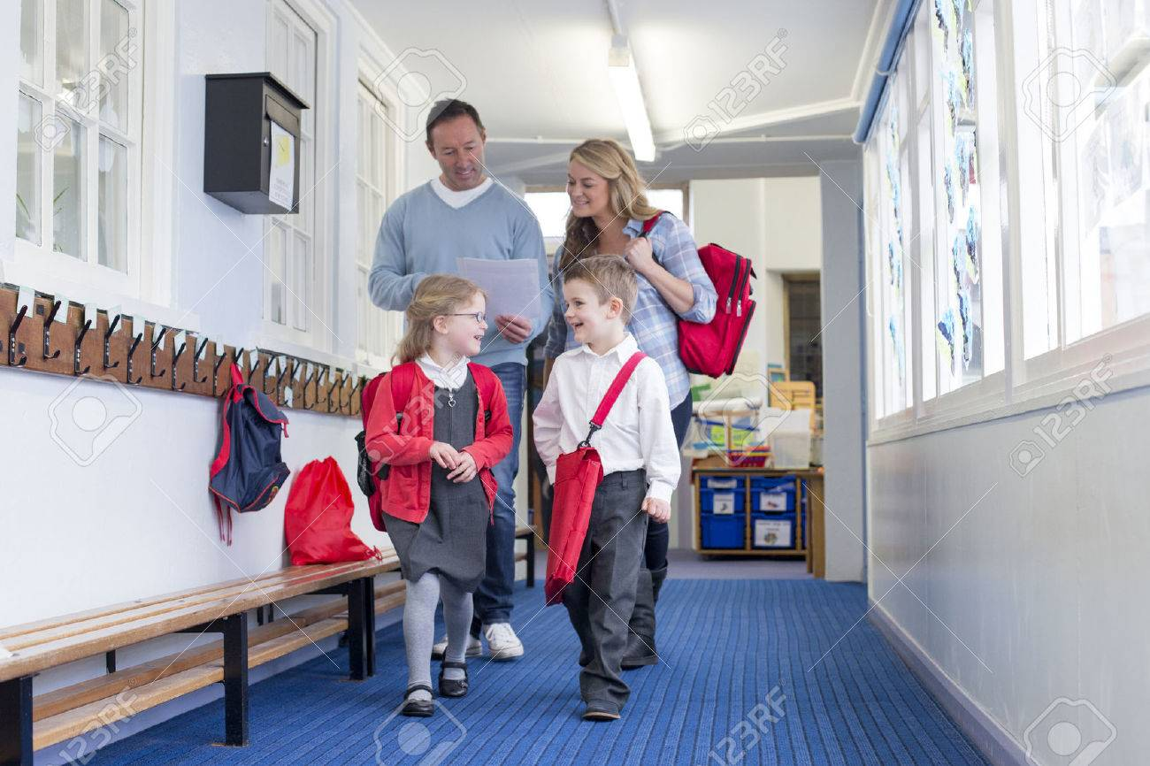 Parents and students walking down a primary school corridor. the parents are looking at some paperwork and the children are talking. - 60255963