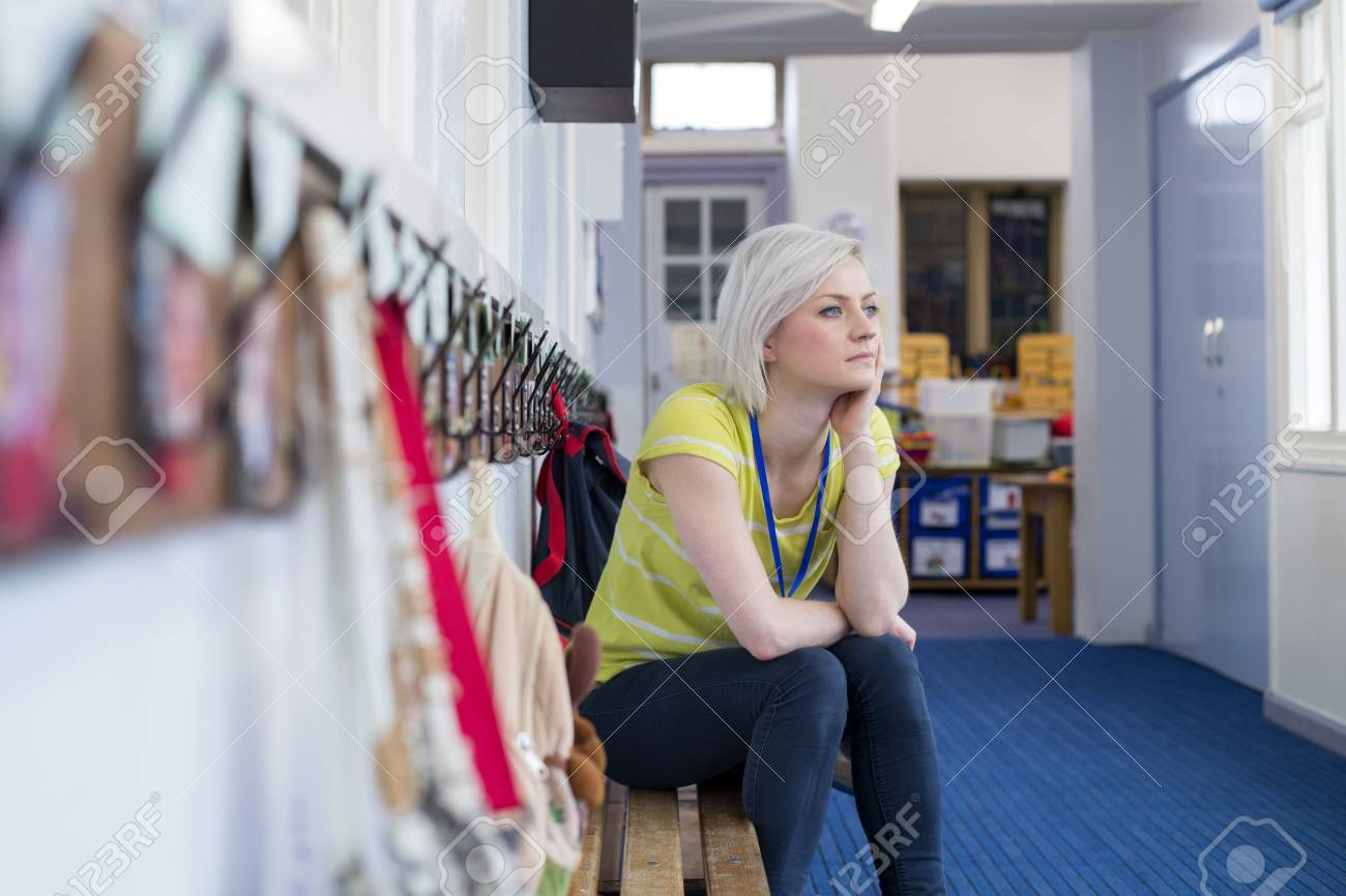 Young, female teacher sitting on a bench in the cloakroom of school. She is looking pensively out of the window. - 60255969