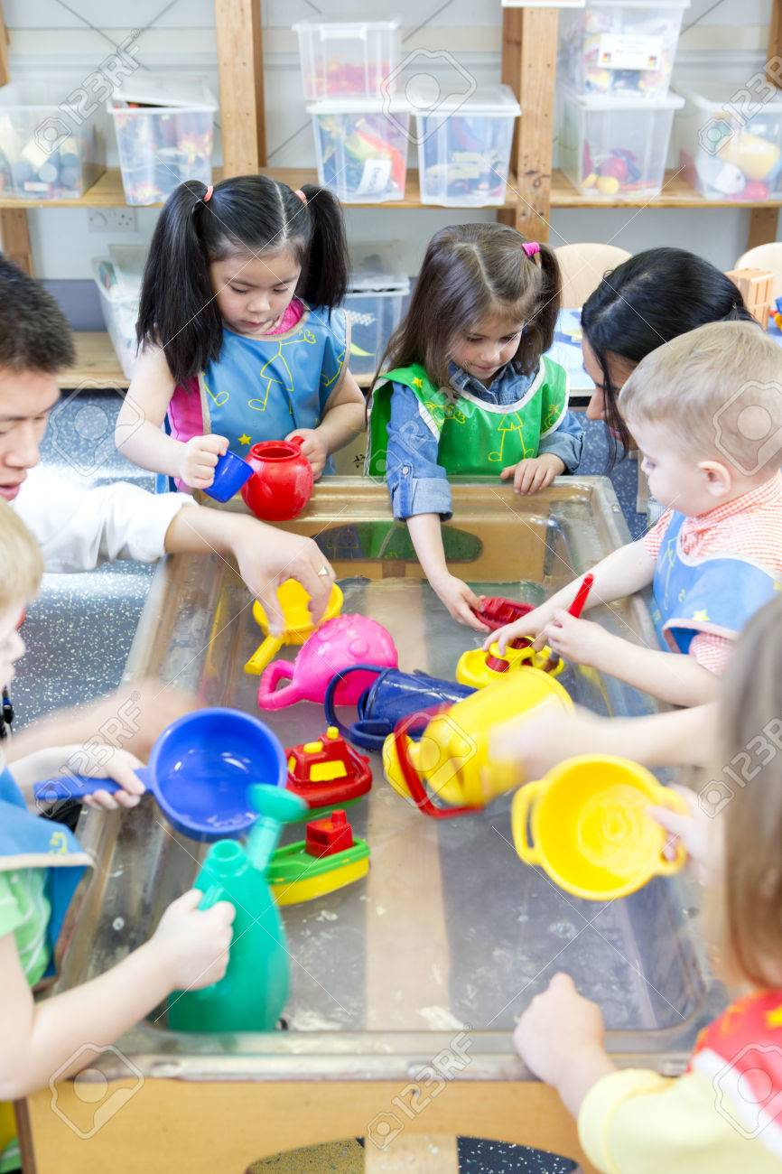 Group of nursery children playing at a water table with their teacher. - 60256175