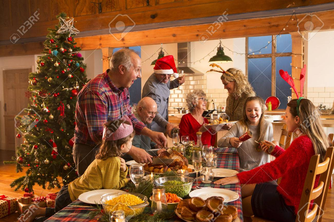 A large family are all helping serve Christmas dinner. - 60248341