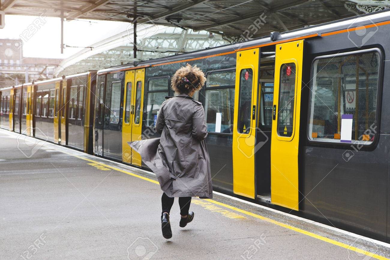 Rear view of a woman running to catch the train before it leaves the station without her. - 65828110