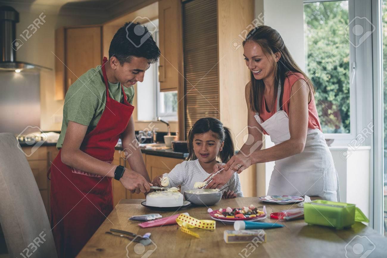 Mutter, Die Einen Kuchen Mit Ihrem Sohn Und Tochter In Der Küche Ihres  Hauses Verziert