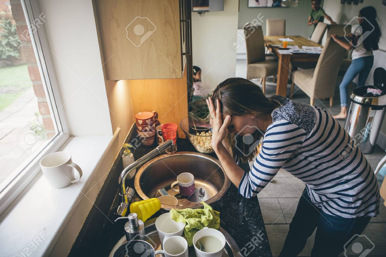 Stressed mum at home. She has her head in her hands at a messy kitchen sink and her children are running round in the background. - 65204958