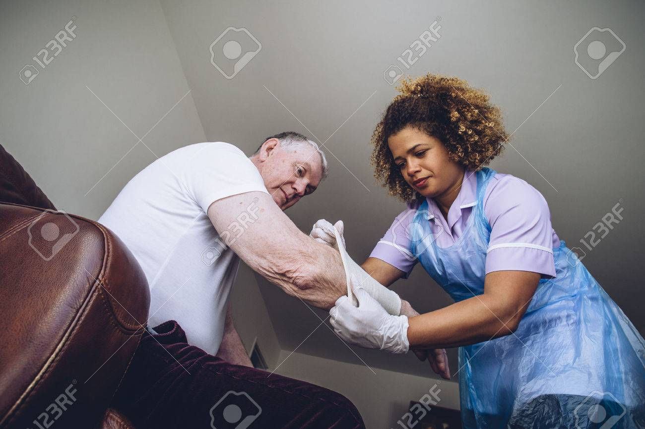 Caregiving Nurse putting a bandage on a senior mans arm in his home. - 65447309