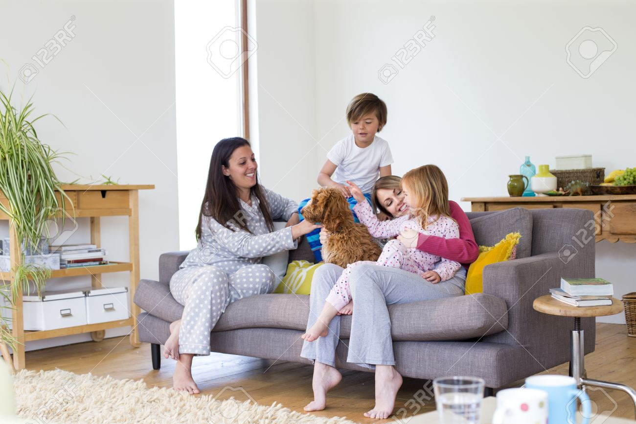 Same Sex Family Together On The Sofa In The Living Room Of Their Home. The