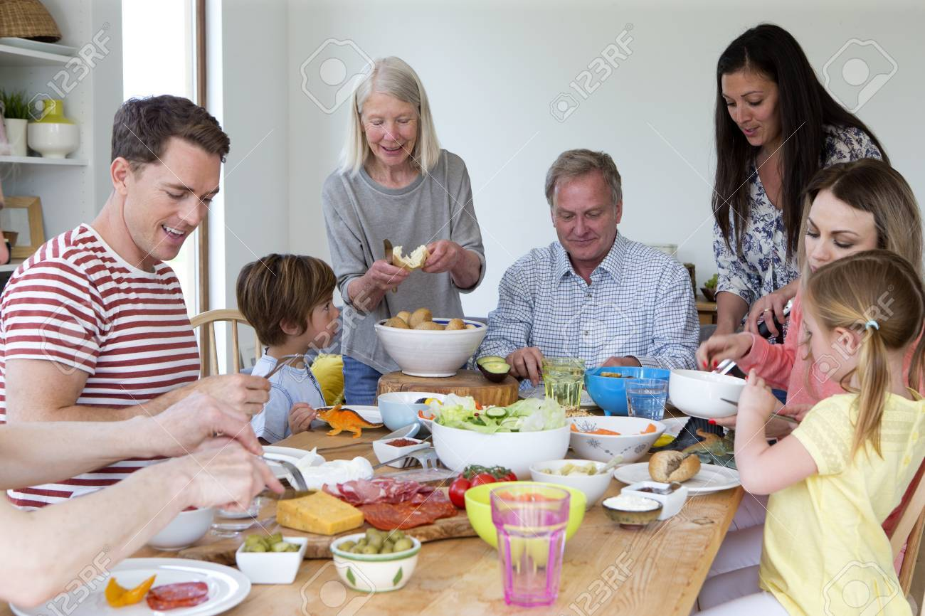 Large Family Are Sat Round A Table In The Dining Room Of A Home. They