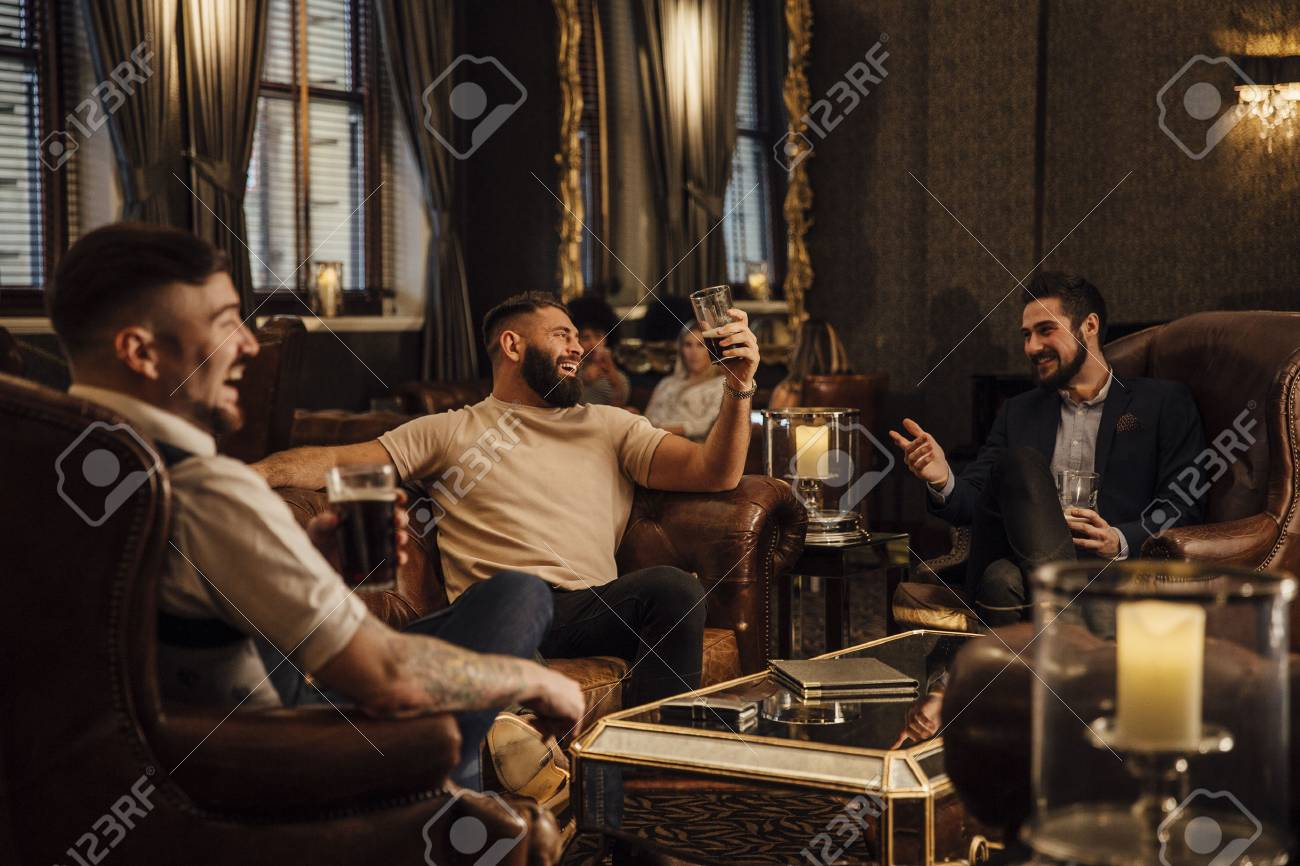 Three men are enjoying drinks in a bar lounge. They are talking and laughing while drinking pints of beer. - 74055608