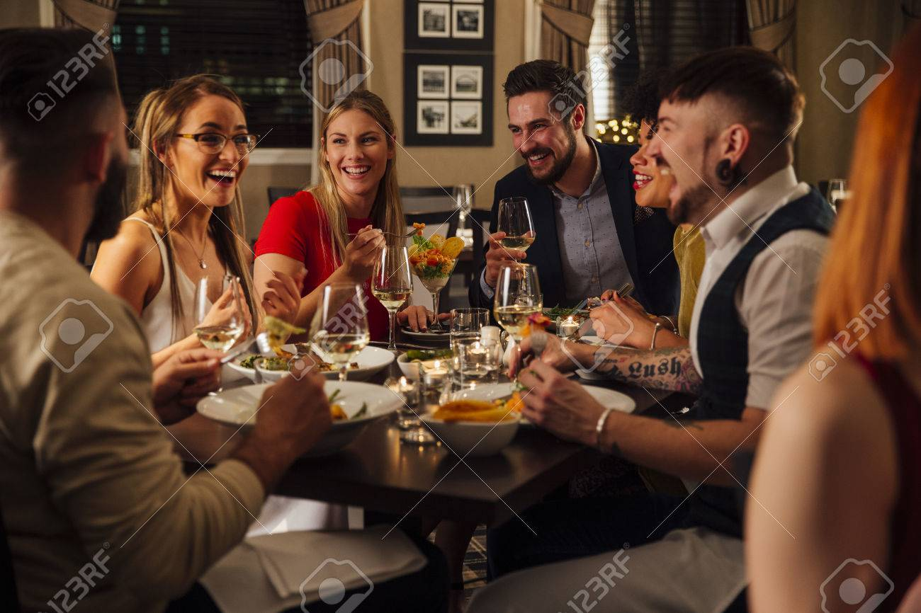 Group of friends are enjoying a meal together. They are talking and laughing while eating their starters and drinking champagne. - 75044752