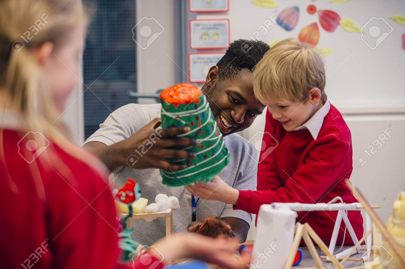 Young teacher is helping one of his primary school students during arts and crafts lesson. - 77181020
