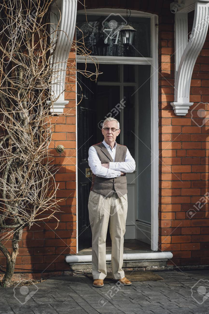 Happy Senior Man Standing Outside The Front Door Of His Home