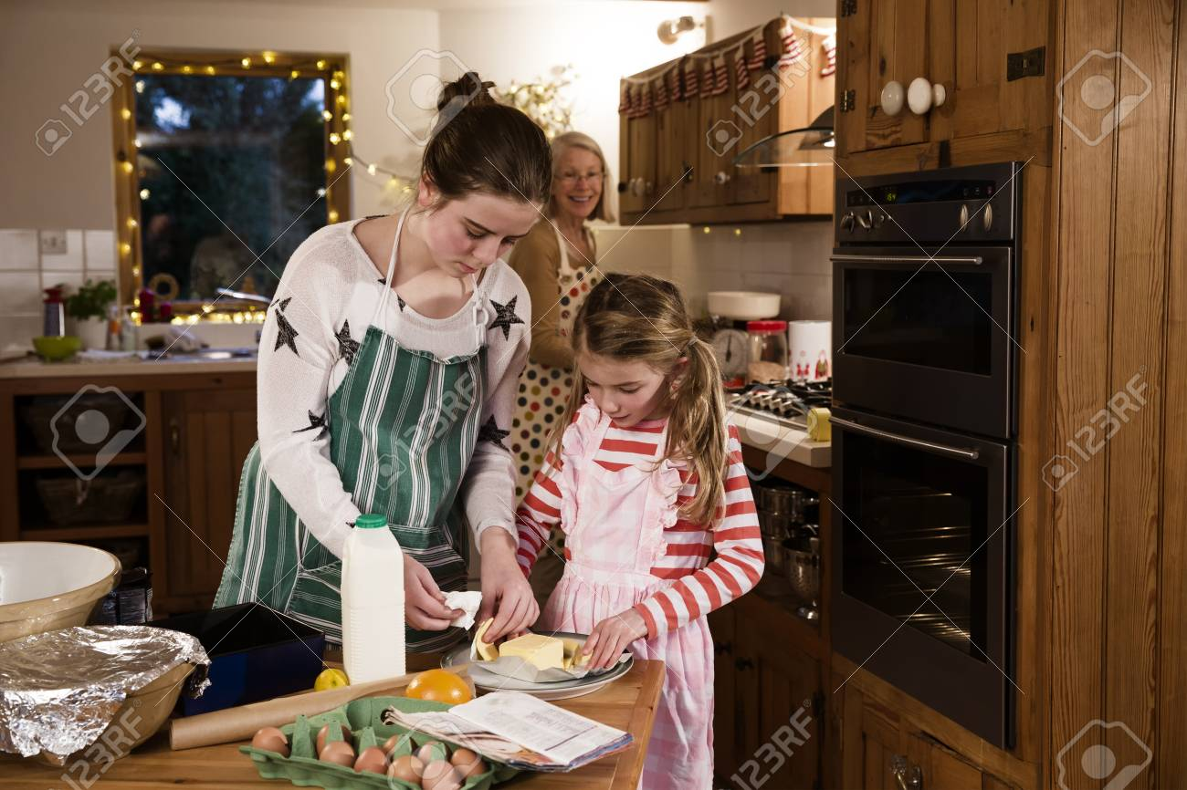 Two sisters are baking cakes in the kitchen with their grandmother...
